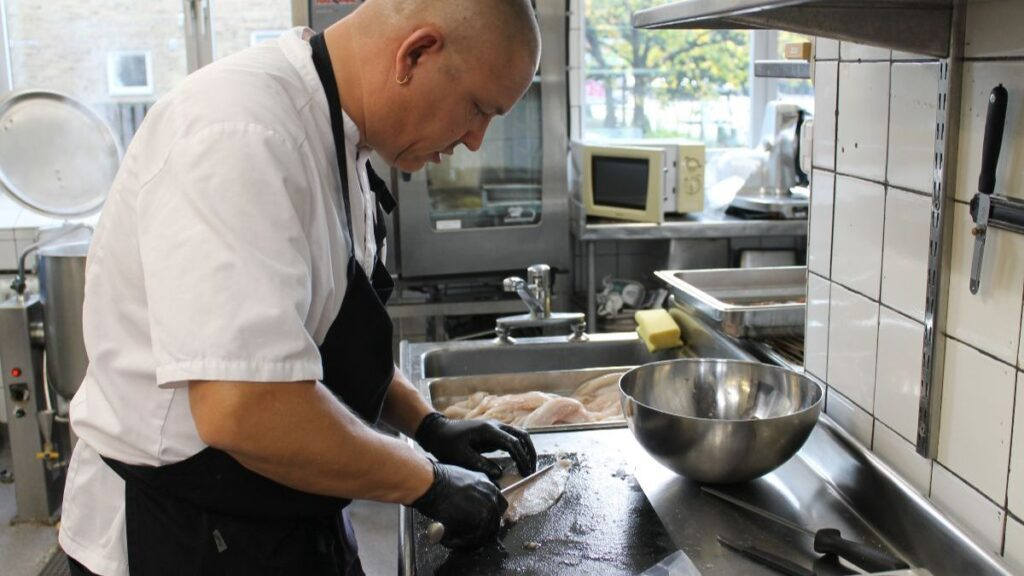 Foto från Livsmedelsakademin på person som tillreder fisk