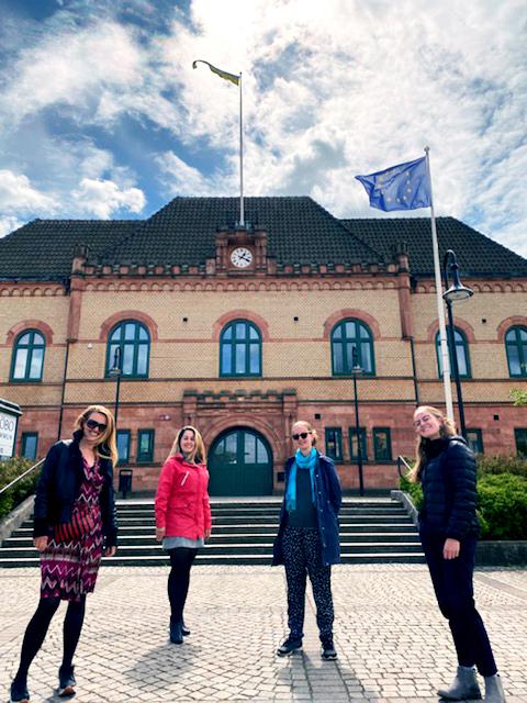 Medarbetare från Europa Direkt Sydskåne och Sjöbo och Tomelillas EU-samordnare framför Sjöbo kommunhus som flaggat för EU-dagen.