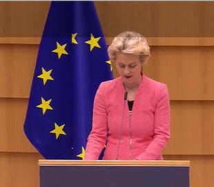 Bild på EU-kommissionens ordförande vid talarstolen framför en EU-flagga